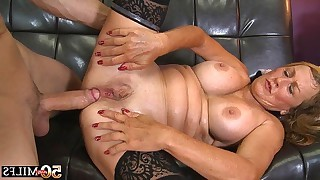 Juicy mature lies on her back and strong man drills her tight asshole on soft couch