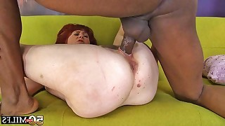 We watch interracial sex action between horny mature and her black lover on couch