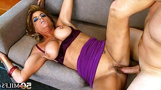 Sexy mature with big tits sucks to later get fucked in her hairy cunt on nice sofa